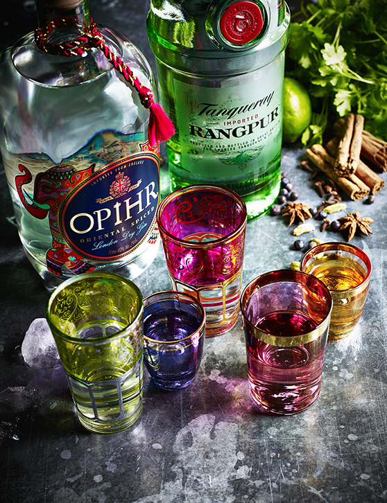 An array of colourful gins from Asia, captured alongside shot glasses ready to pour