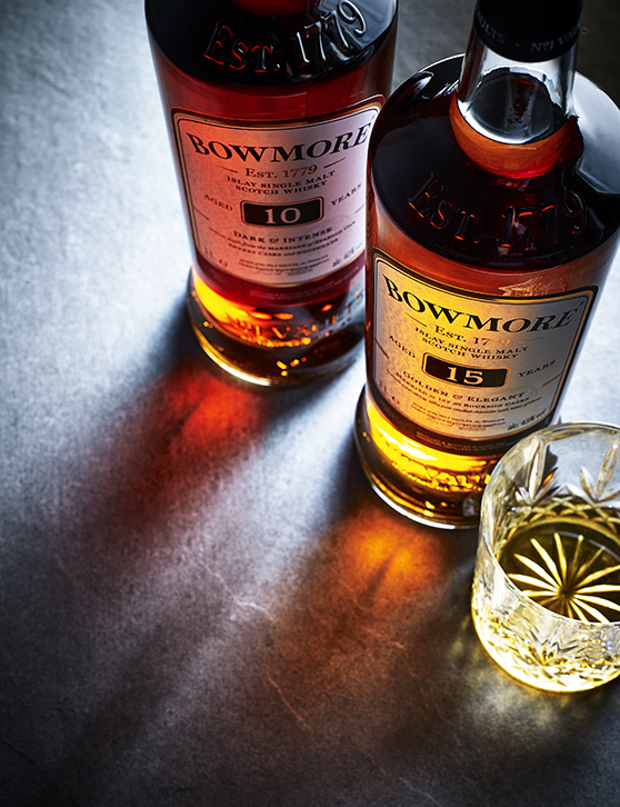 Two bottles of single malt whiskey, Bowmore, aligned casting a shadow onto the surface