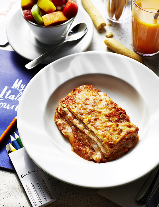 Lasagne, surrounded by cutlery and side dishes